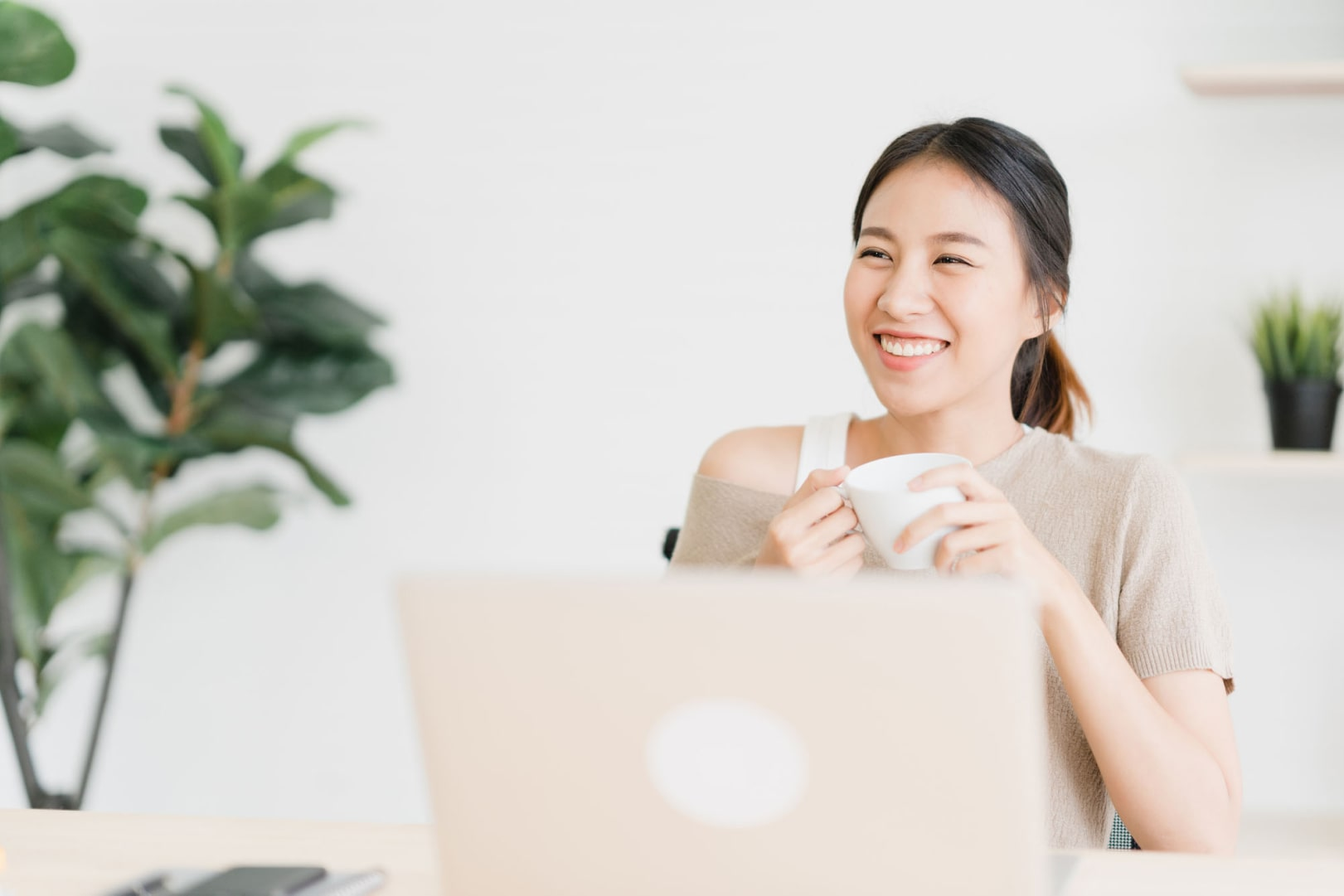 beautiful-young-smiling-asian-woman-working-laptop-drinking-coffee